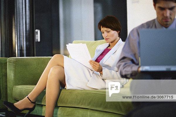 Weibliche Führungskraft beim Lesen von Dokumenten auf dem Sofa  Mann bei der Arbeit am Laptop im Vordergrund