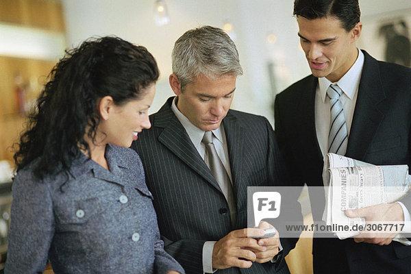 Geschäftsfreunde  die zusammenstehen und auf das Handy schauen