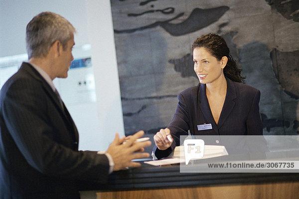 Rezeptionist im Gespräch mit Geschäftsmann