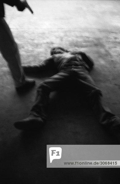 Person  die die Waffe auf einen auf dem Boden liegenden Mann hält.