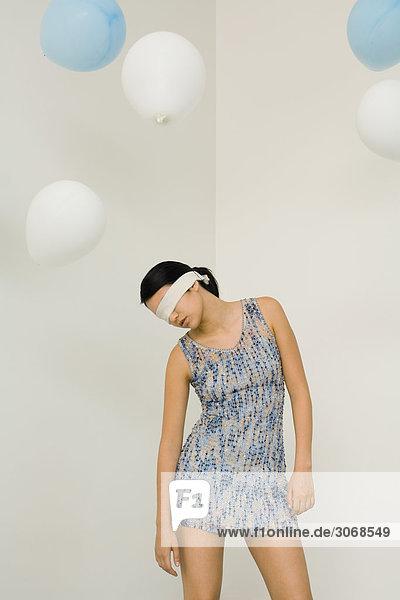 Frau mit verbundenen Augen  Kopf nach unten  Luftballons schweben über dem Kopf.