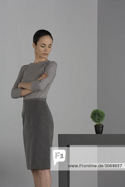 Frau steht neben dem Tisch mit gefalteten Armen und schaut über die Schulter auf die Topfpflanze.