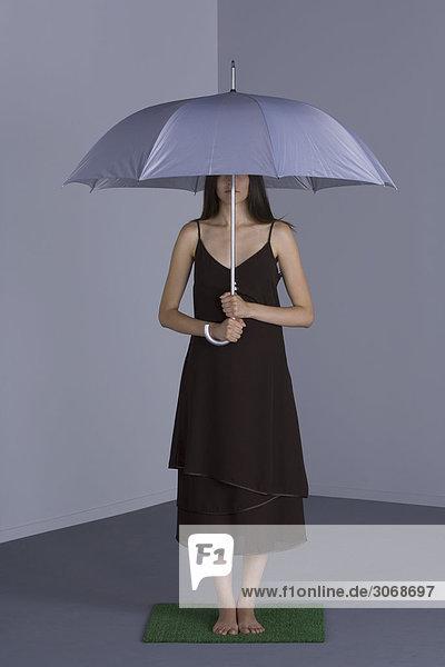 Weibchen steht unter Schirm auf Kunstrasen  Gesicht teilweise verdunkelt