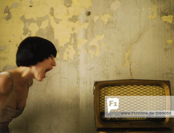 Frau  die sich dem altmodischen Radio zuneigt  schreit  schaut aus dem Fenster.