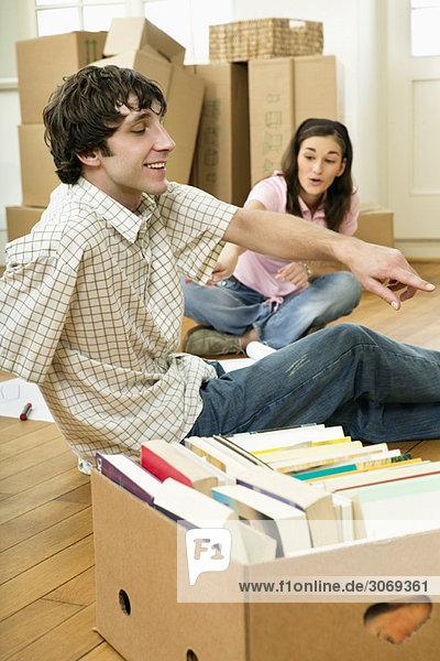 Junges Paar beim Umzug mit Bücherkarton und Meterstab auf Holzboden