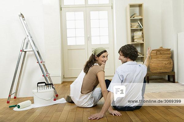 Junges Paar in leerer Wohnung beim Streichen  hält sich an den Händen