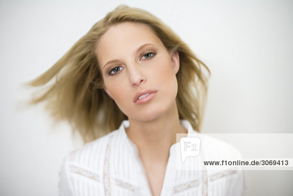 Junge blonde Frau mit weißer Bluse blickt in Kamera  Hintergrund unscharf