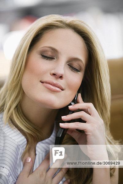 Junge Frau telefoniert sitzend vor beigem Sofa  Hand am Herzen