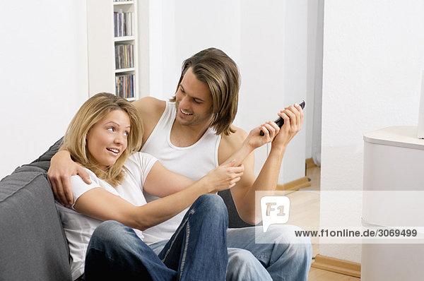 Junges Paar streitet sich auf Sofa um Fernbedinung für Fernseher