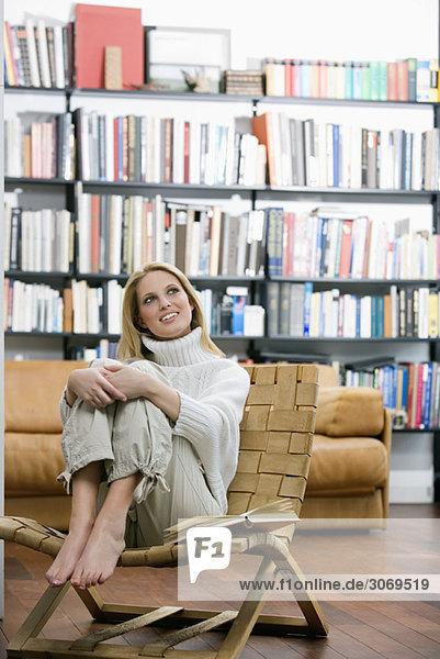 Junge Frau sitzt in Sessel  hohe Bücherregale im Hintergrund
