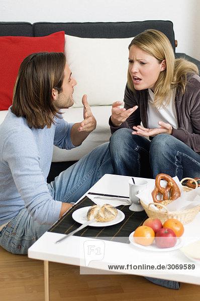 Junges Paar vor Sofa beim Frühstück streitet sich
