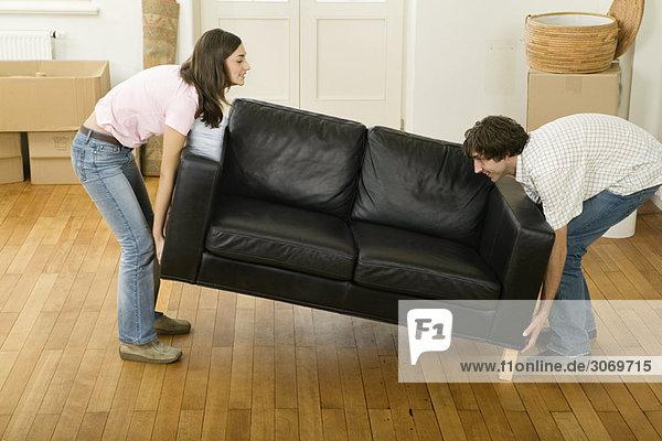 Junges Paar beim Umzug hebt Sofa an