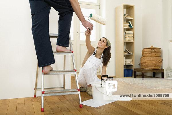 Mann auf Leiter in Wohnung beim Streichen  Frau reicht Farbrolle