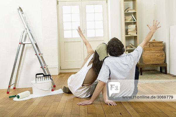 Junges Paar in leerer Wohnung beim Streichen  Rückansicht