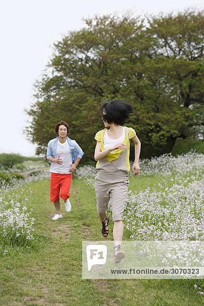 Junges Paar läuft durchs Feld
