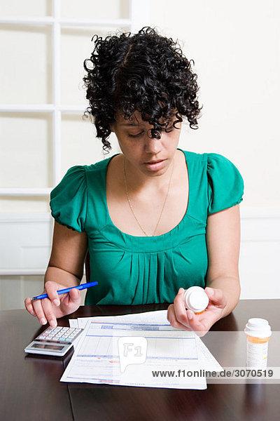 Frau mit Rechnungen und Tabletten mit Taschenrechner