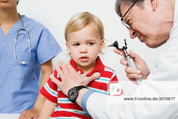 Arzt schaut in das Ohr des Jungen