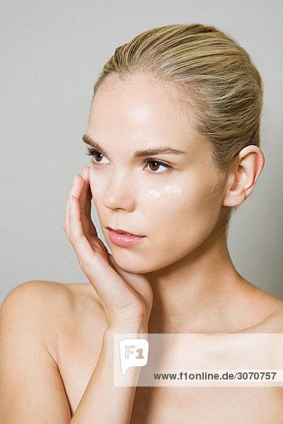 Junge Frau mit Feuchtigkeitscreme im Gesicht