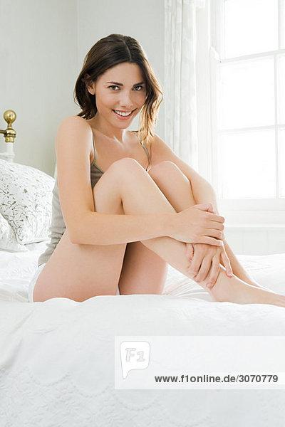 Junge Frau auf dem Bett sitzend