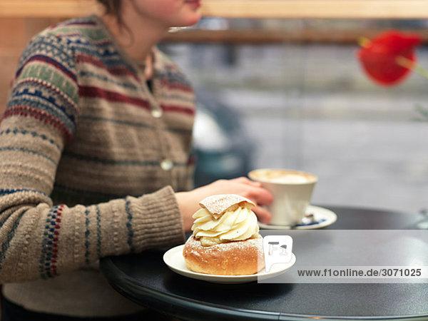 Junge Frau ein Stück Gebäck in einem Café Schweden Essen.