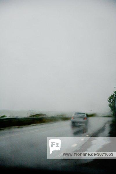 Ein Auto auf der Straße im Regen Schweden.