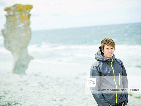 Ein Mann auf einem Kiesstrand Gotland Schweden.
