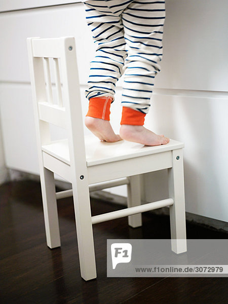 The legs of a girl standing on a chair Sweden