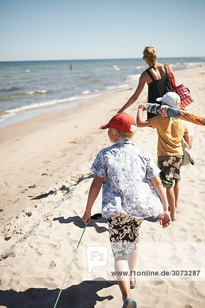 Mother and sons walking on a beach Gotland Sweden.