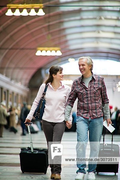 A couple with suitcases at a railway station