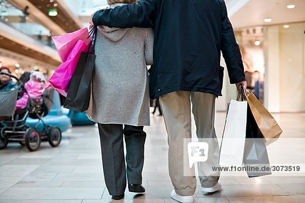 Senior couple carrying shopping bags Stockholm Sweden.