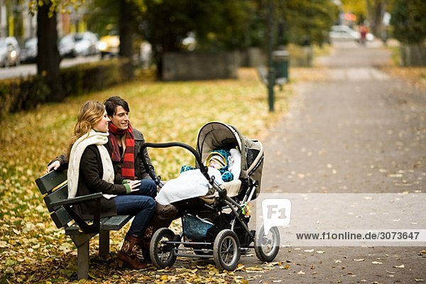 A couple siting with their son in a park Sweden.
