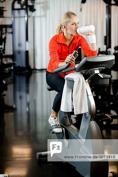 A woman doing indoor cycling at a gym Sweden.