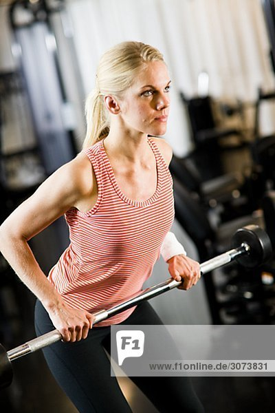 A woman weight training at a gym Sweden.