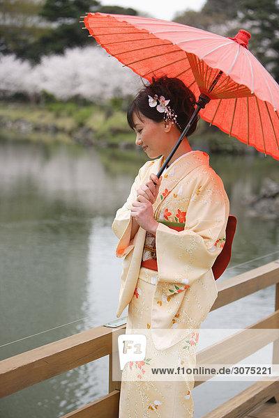 stehend Frau halten Sonnenschirm Schirm Holzbrücke