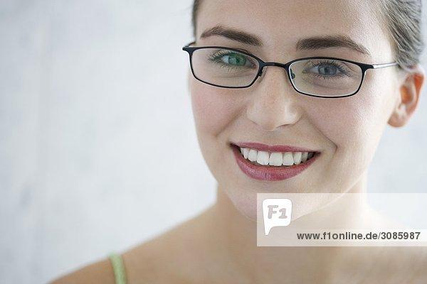 Portrait einer jungen Frau mit Brille  lächelnd  Kamera