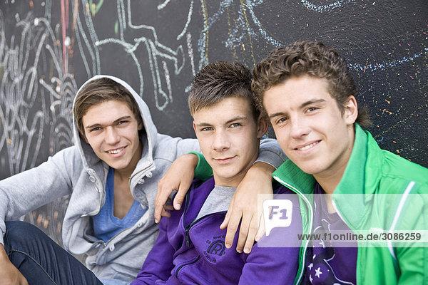 Drei Jungen sitzen nebeneinander vor einer Wand  Close-up