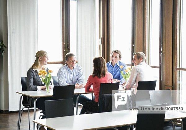 Fünf Personen sitzen am Tisch