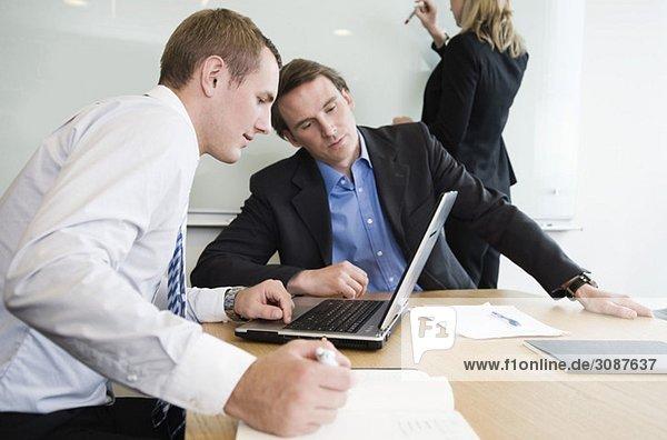 Zwei Männer und eine Frau im Konferenzraum