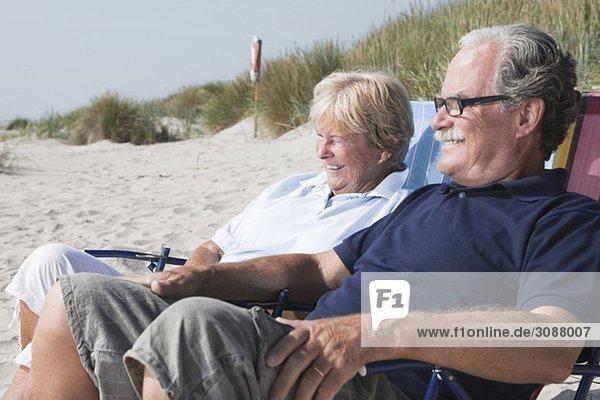 Zwei Leute sitzen am Strand.
