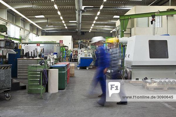 Zwei Arbeiter  die durch eine Fabrik gehen  verschwommene Bewegung  lange Belichtung