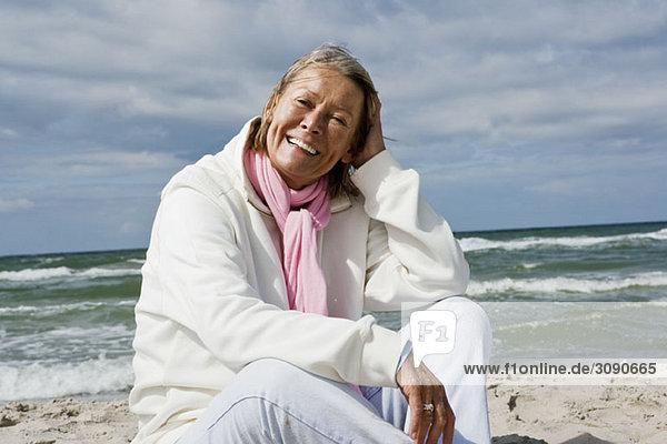 Eine ältere Frau  die am Strand sitzt.