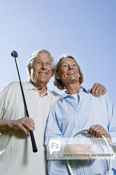 Ein älteres Paar mit einem Golfschläger und einem Tennisschläger.