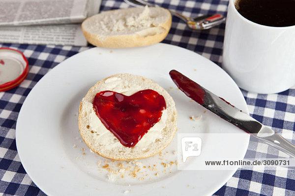 Eine Rolle mit Marmelade in Herzform Eine Rolle mit Marmelade in Herzform