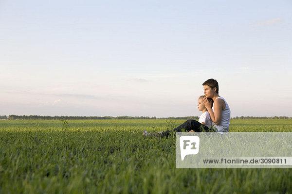 Seitenansicht einer Frau und eines Mädchens  die zusammen auf einem Feld sitzen
