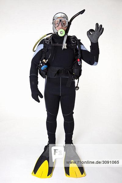 A scuba diver giving the OK sign  studio shot