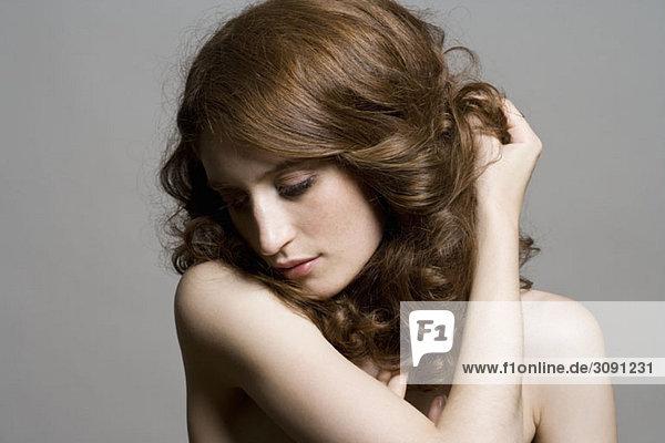 Porträt einer Frau  die ihr Haar zurückhält.