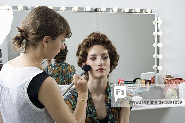 Ein Maskenbildner  der Make-up auf ein Modell aufträgt.