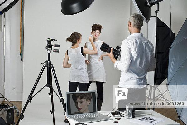 Fotograf  Model und Maskenbildner am Set eines Modeshootings