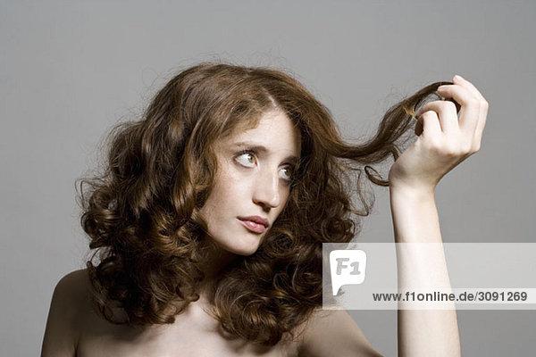 Eine junge Frau  die ihr Haar ansieht.