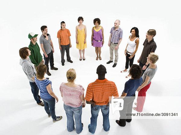 Eine Gruppe von Männern und Frauen  die einen Kreis bilden.